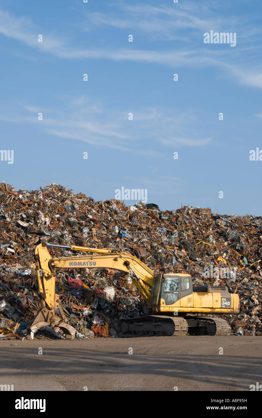 A pile of  scrap metal  ready for recycling, with dormant machinery in the foreground - Stock Image