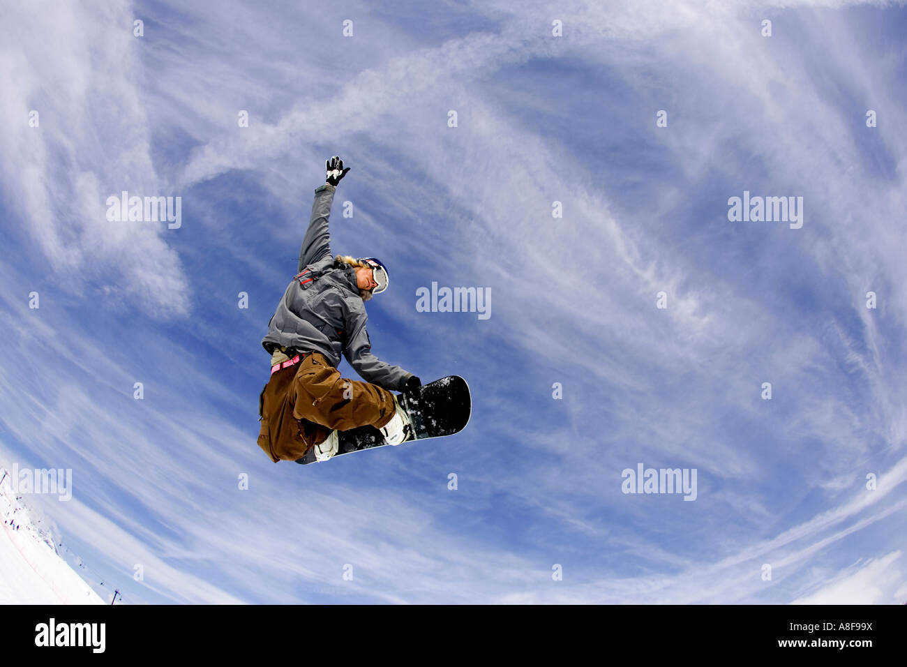 Snowboarder grabs board flying through alpine air. - Stock Image