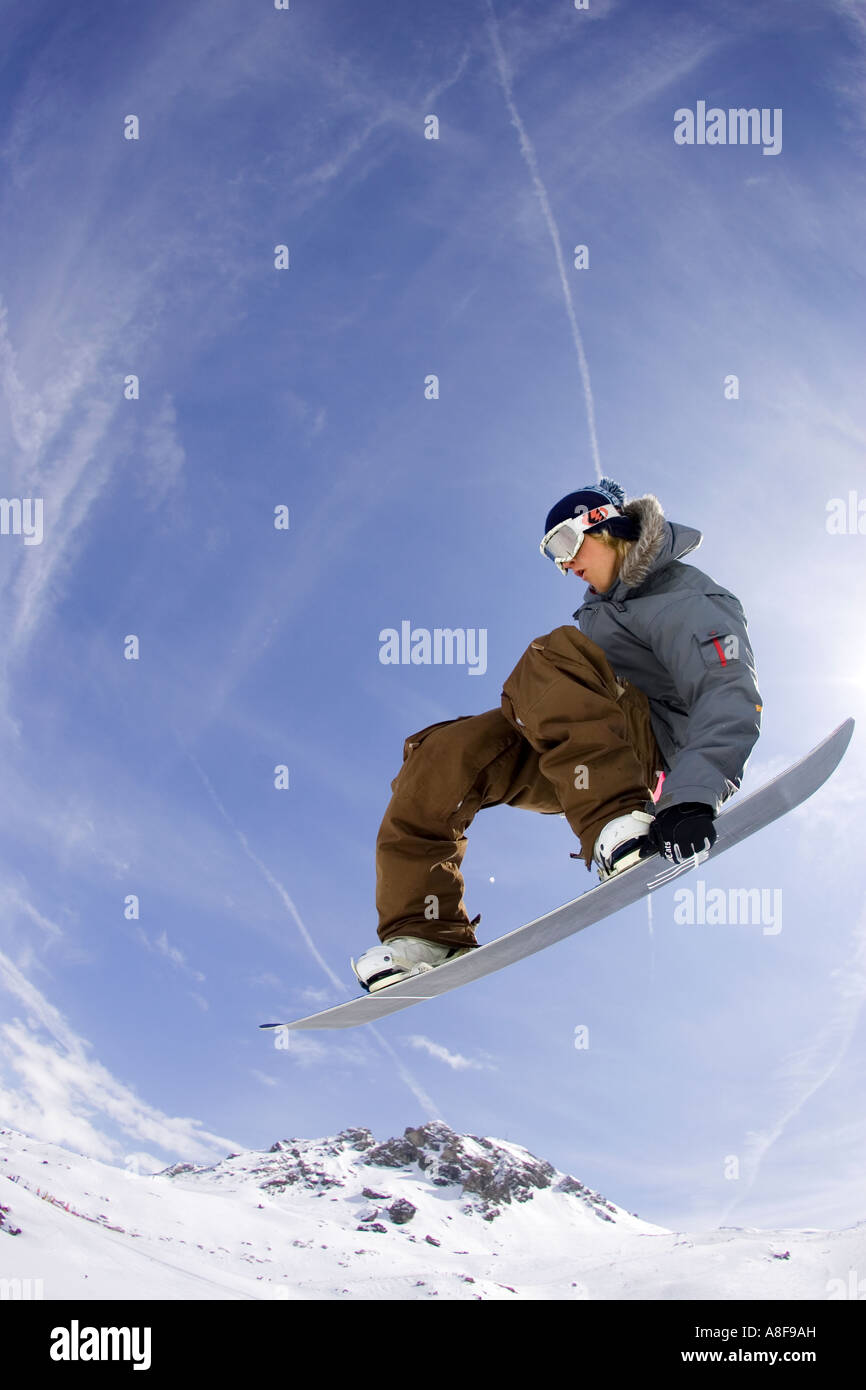 Snowboarder mid air grabs board. - Stock Image