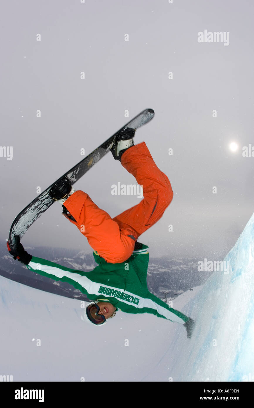 Snowboarder inverted in half pipe grabbing board - Stock Image