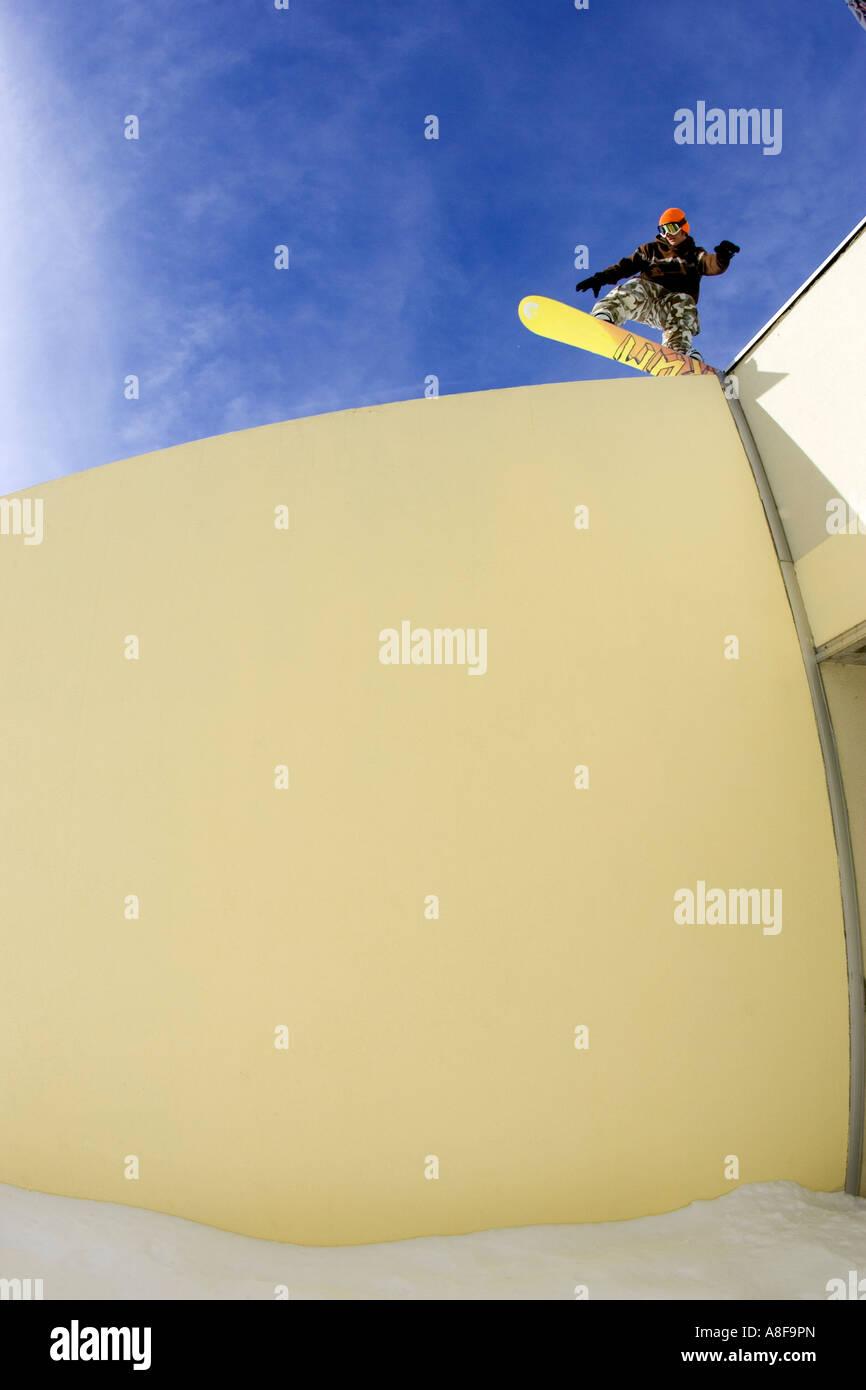 Snowboarder sliding a wall. Stock Photo