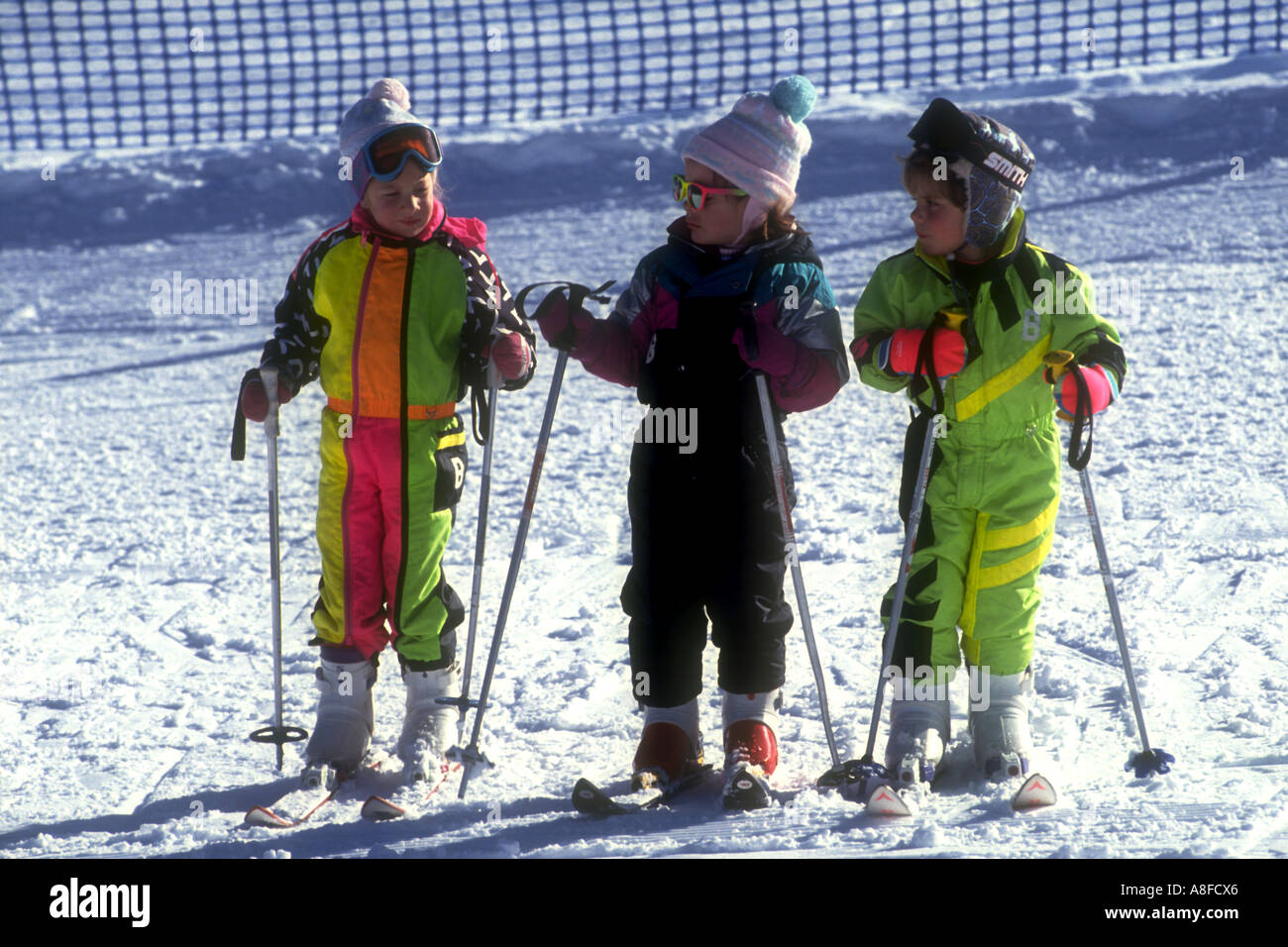 Three very young little girls dressed in colorful ski suits, learning to ski at Snow Summit ski resort, Big bear, CA.USA - Stock Image