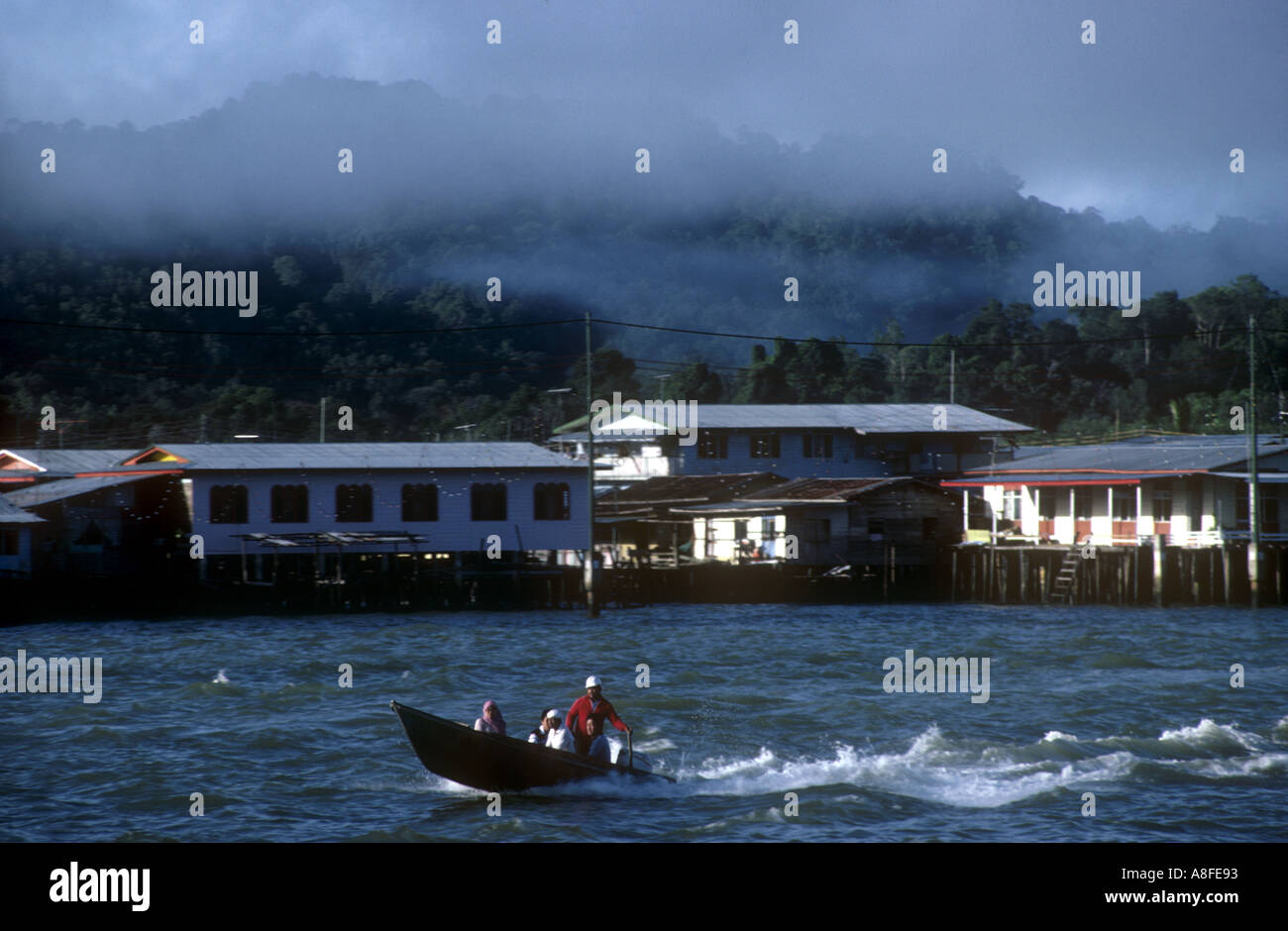 BRUNEI Bandar Seri Begawan Kampong Floating Village Early morning mist rising from jungle behind as water taxi passes on river - Stock Image