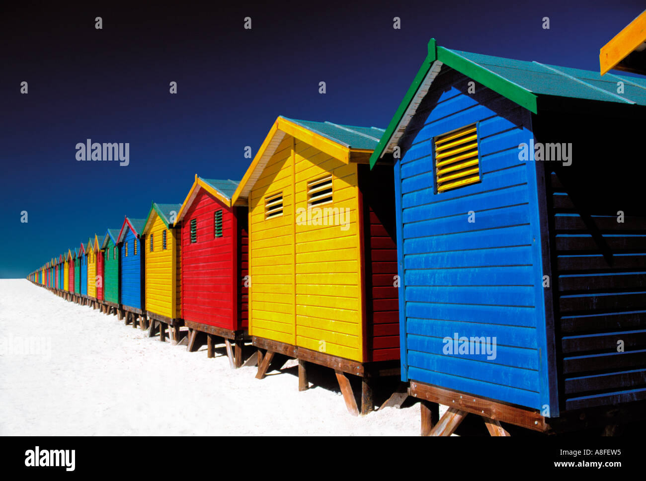 brightly-coloured beach huts on beach, Muizenberg, Cape Town, South Africa Stock Photo