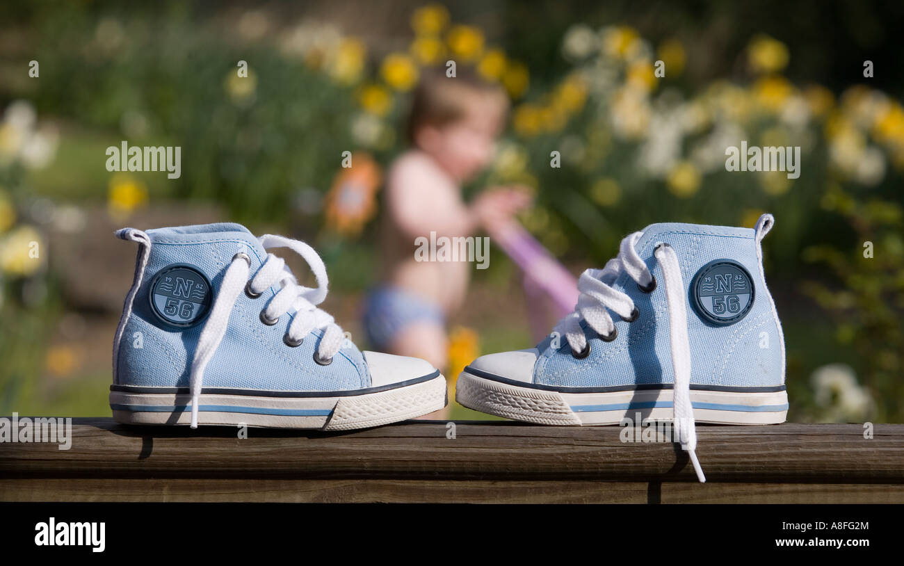 A pair of young boys pumps with toddler out of focus in the background - Stock Image