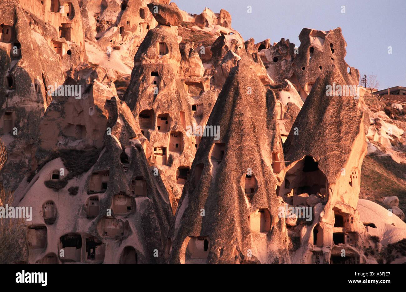 Cappadocia a surreal landscape of cones pillars hollowed out dwellings Uchisar Cappadocia C Anatolia Turkey Sunset glow - Stock Image