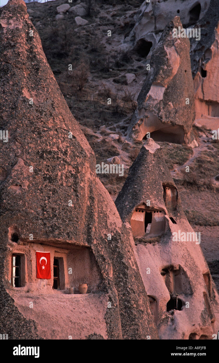 Cappadocia A surreal landscape of cones pillars hollowed out dwellings Uchisar C Anatolia Turkey Turkish flag outside a home - Stock Image