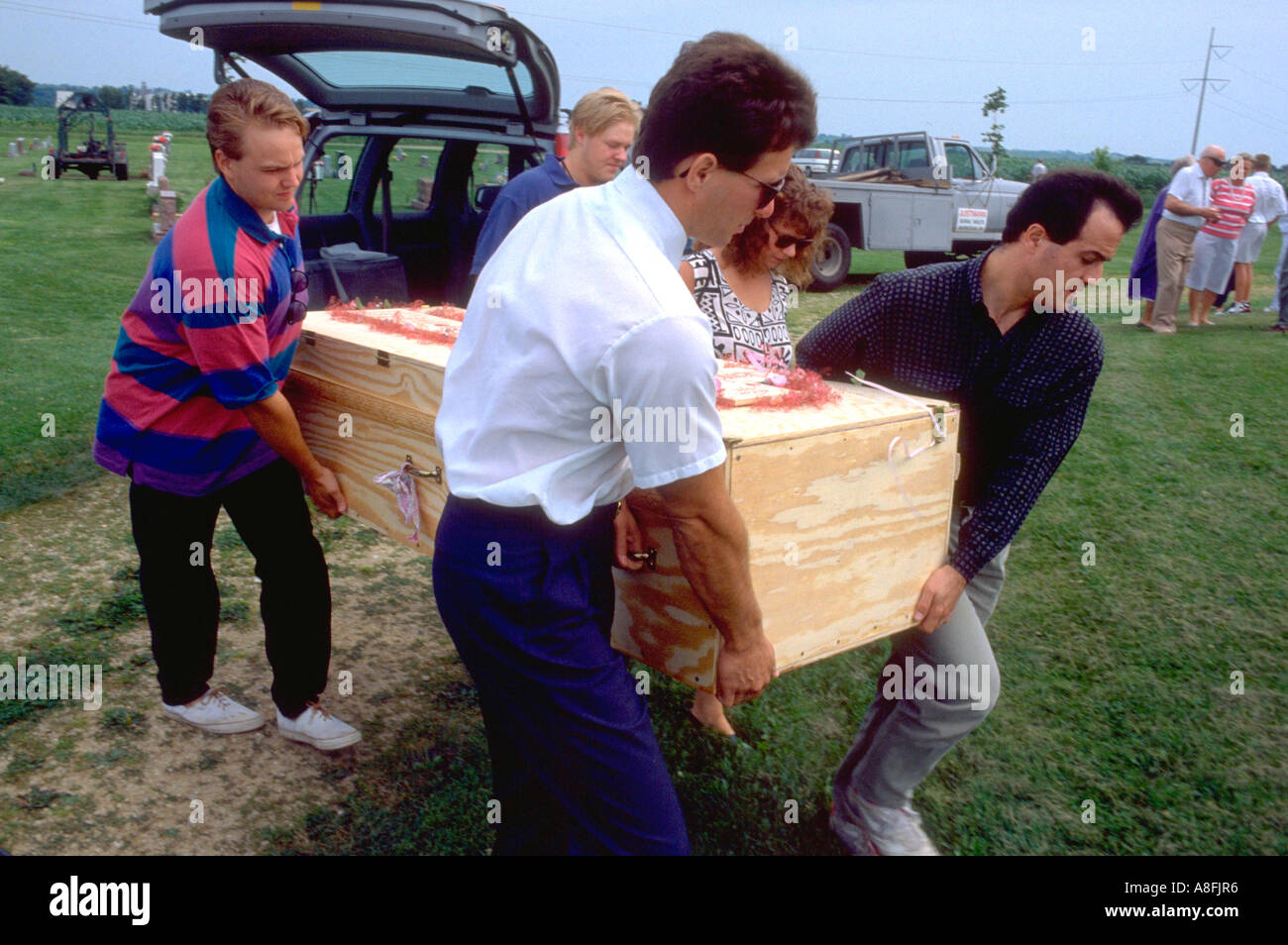 Pallbearers age 32 carrying grandma's plywood coffin to the grave. Cambria Wisconsin USA - Stock Image