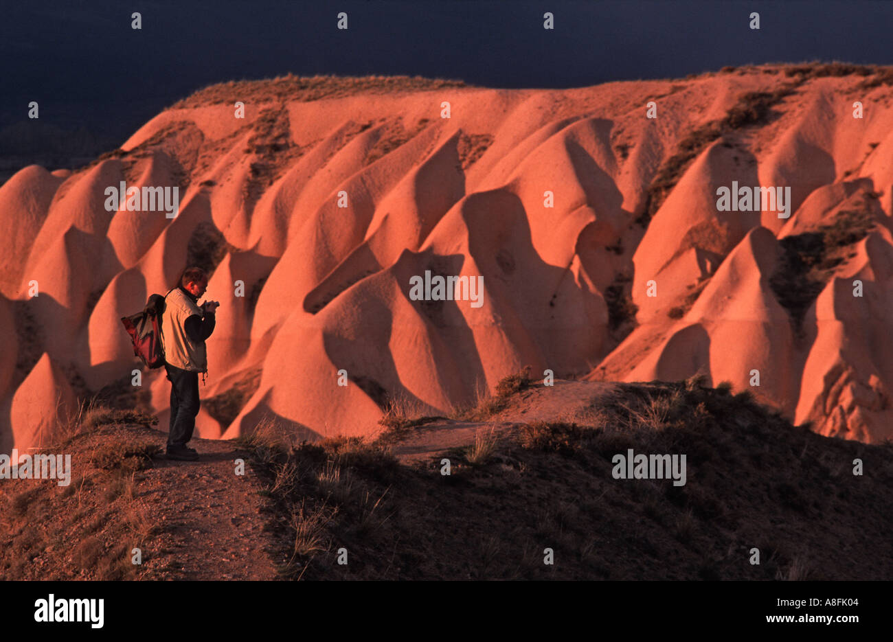 Photographer with backpack and camera standing facing spectacular formations near Uchisar Cappadocia Anatolia Turkey Sunset - Stock Image