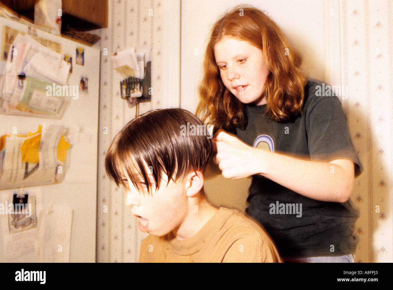 Sister Cutting Brother S Hair In Kitchen Stock Photo Alamy