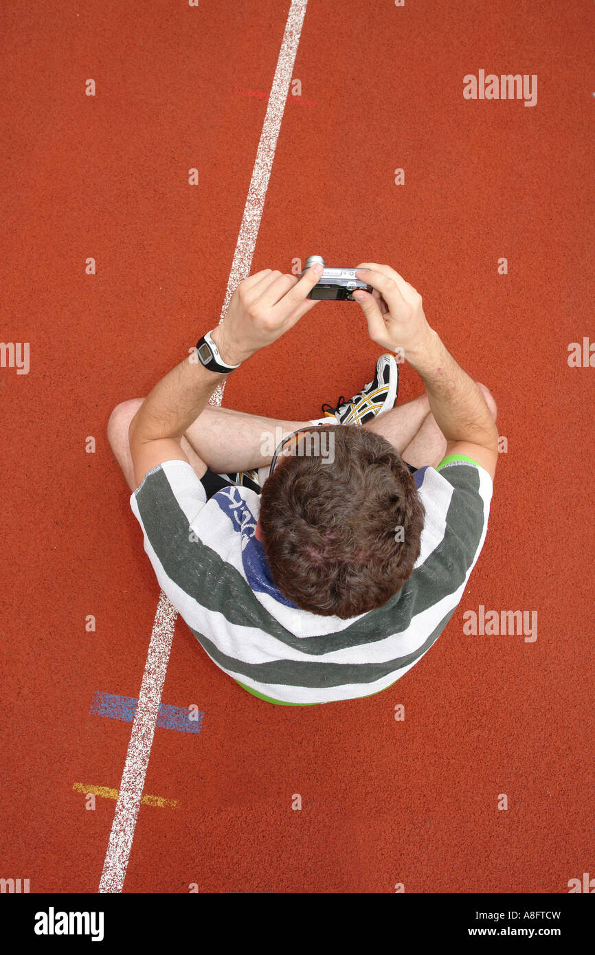 Man taking photo with digital camera on running track - Stock Image