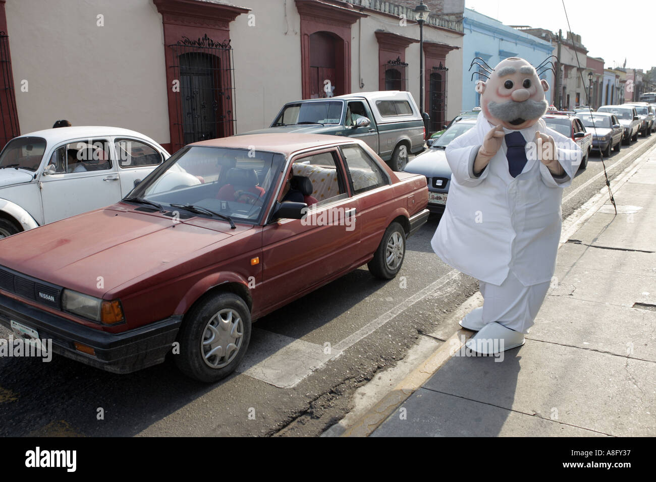 A person dressed as a cartoon character waves to cars and pedestrian as part of a promotion for a pharmacy in Oaxaca Stock Photo