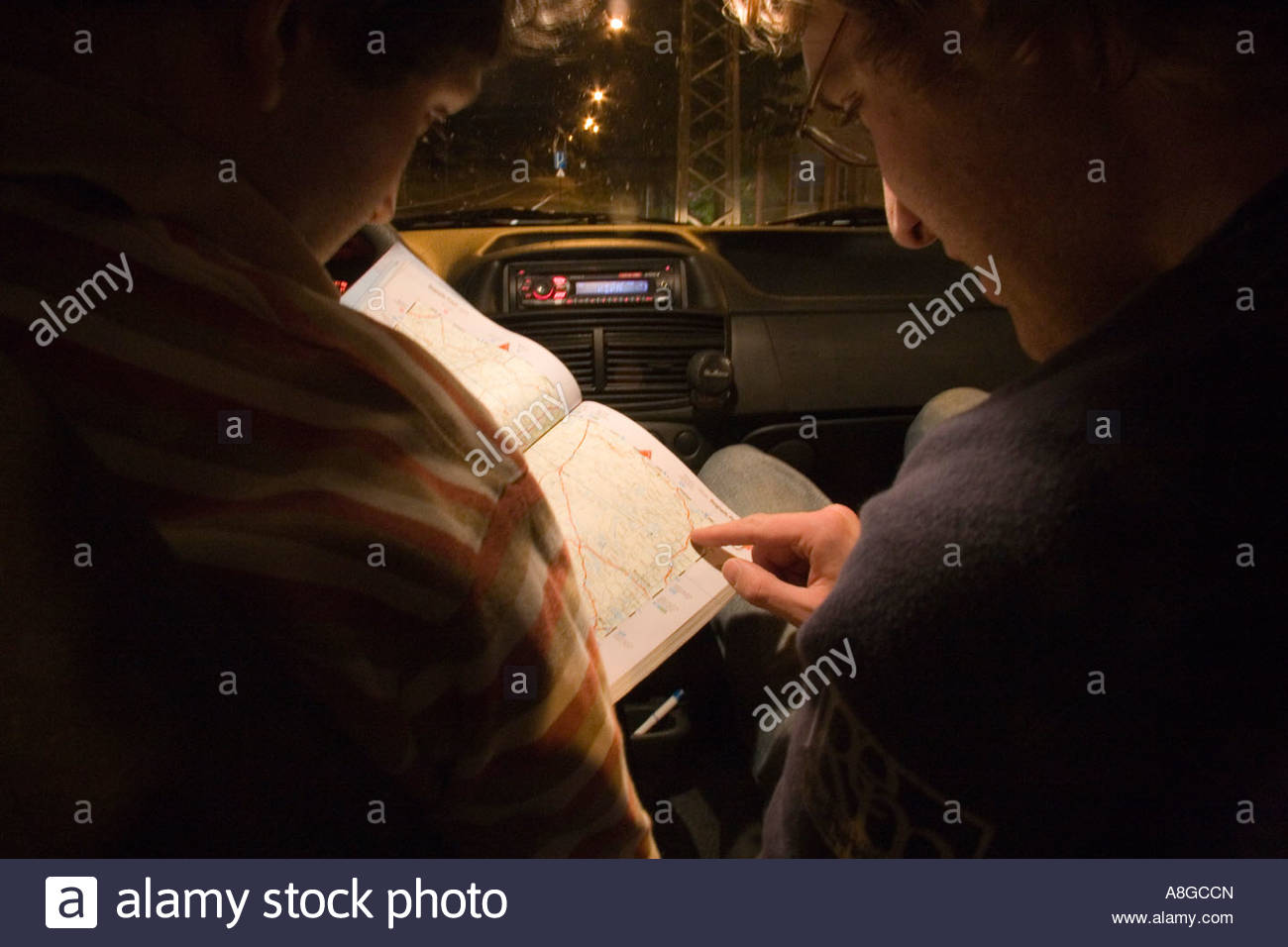 Lost tourists in a car during the night, checking their road atlas, in Europe. - Stock Image