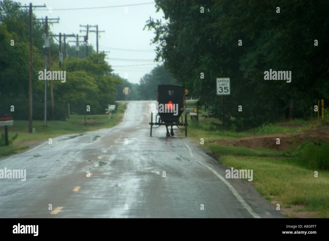 Soft Focus View of Amish Carriage through Vehicle Windshield on Rain Slicked Road Stock Photo