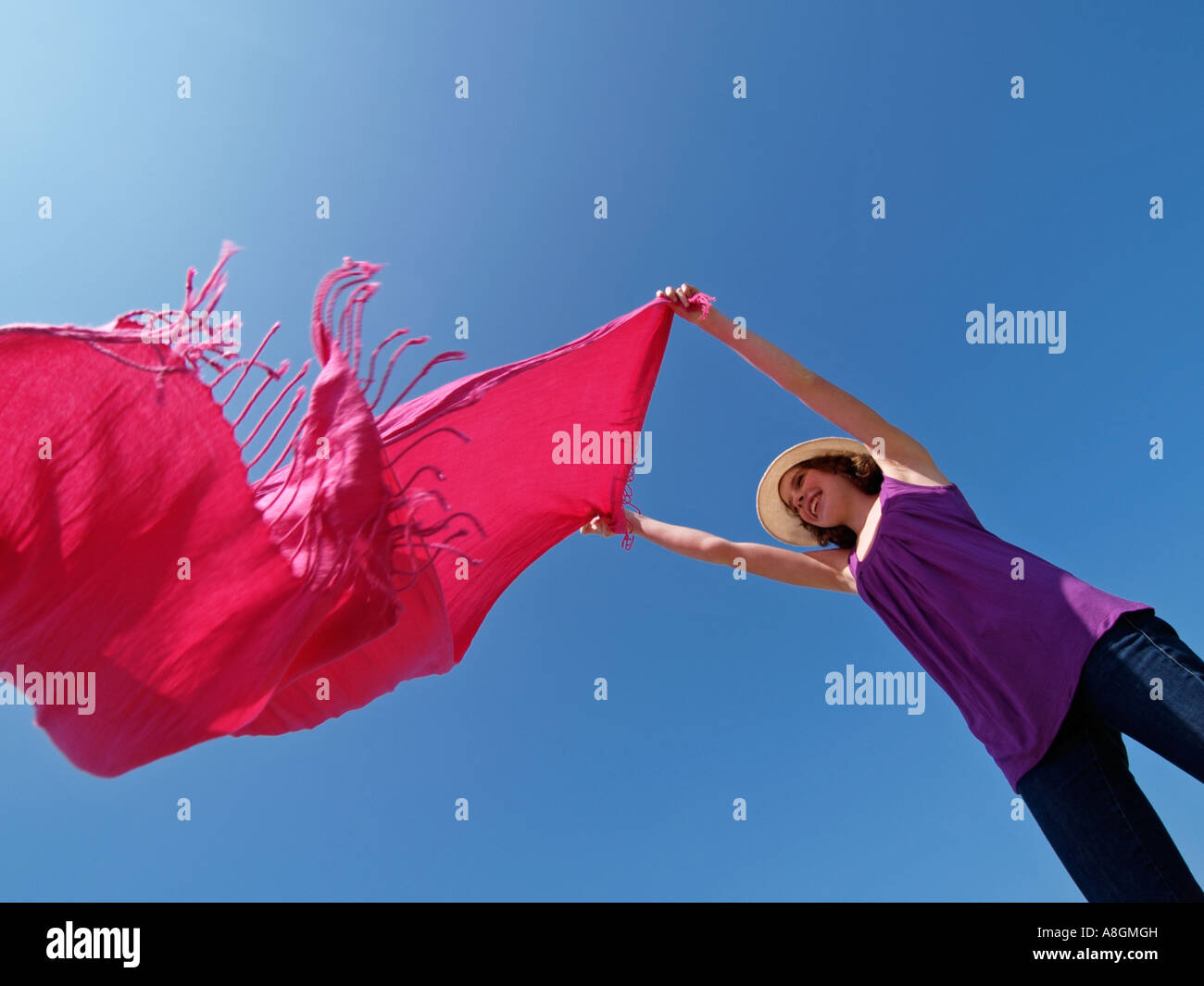 Teenage girl young woman waving big pink scarf against blue sky wind summer fun - Stock Image