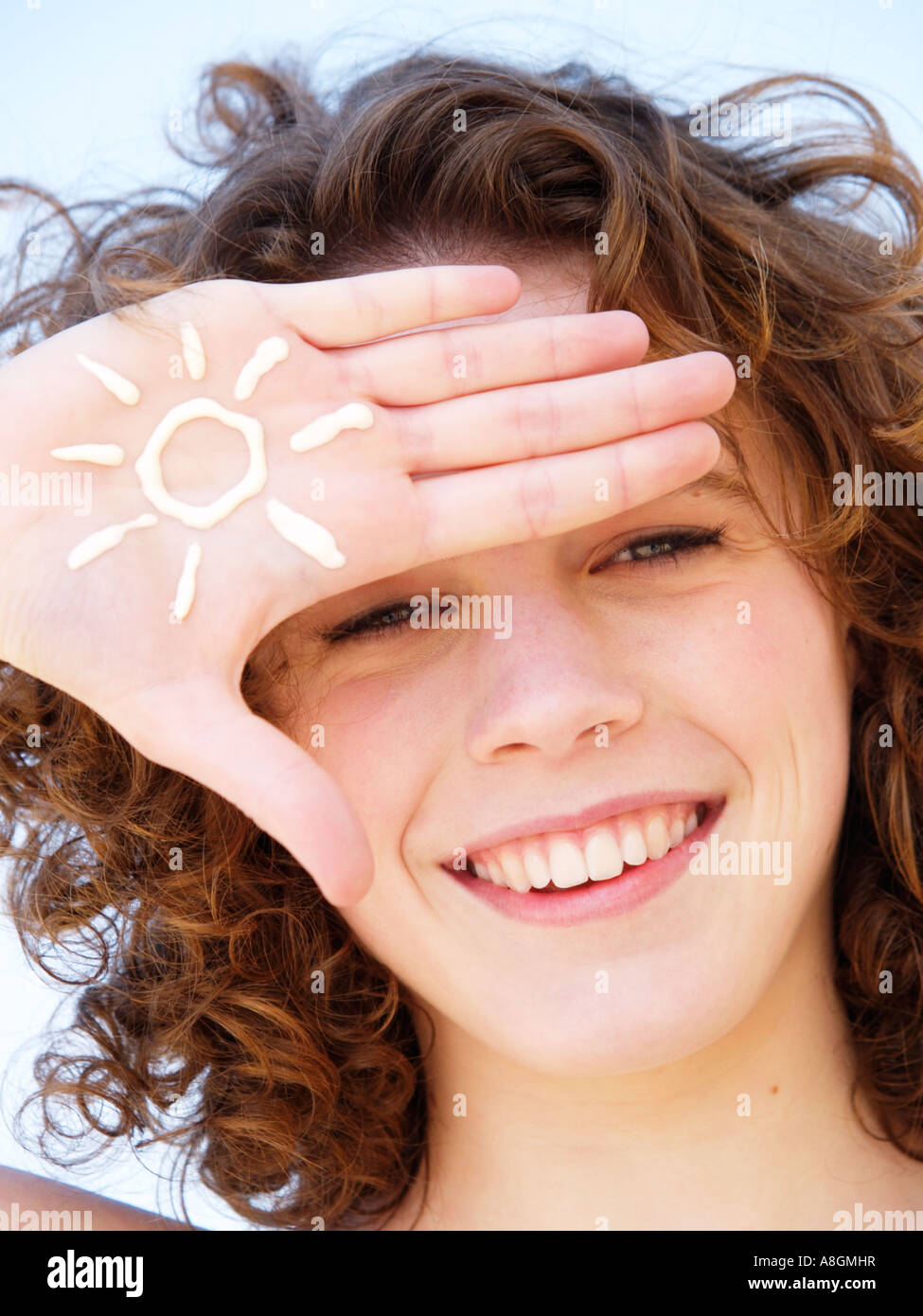 Teenage girl smiling with figure of a sun drawn in suncream on her hand Light skin needs to be protected against - Stock Image