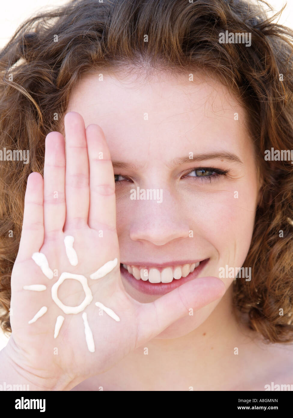Young woman smiling with figure of a sun drawn in suncream on her hand Fair skin needs to be protected against uv - Stock Image