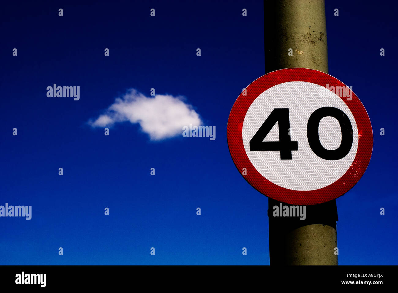 road sign 40 miles per hour speed limit against dark blue sky with a single fluffy white cloud in the background - Stock Image