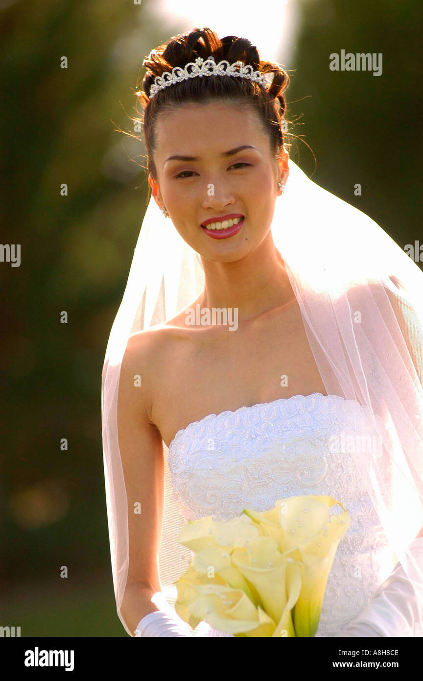 Portrait of Asian bride in wedding dress with tiara in her hair and ...