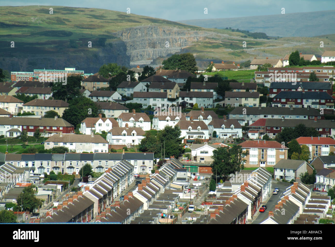Suburbs of Merthyr Tydfil looking down semi aerial view housing estates with quarry face in hillside distant - Stock Image