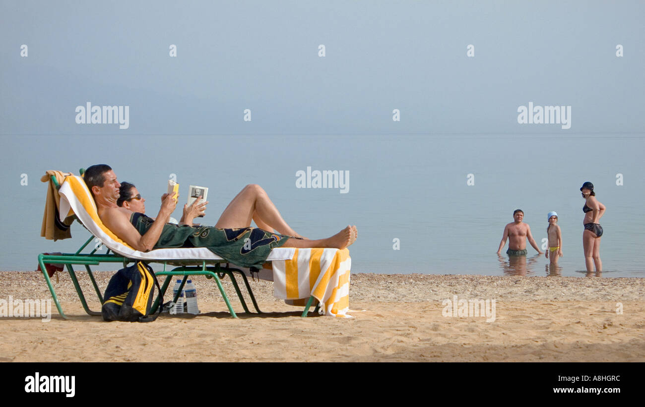 Holidaymakers relaxing on sun loungers whilst reading Family at the shore Beach beside the Red Sea at Nuweiba Sinai Egypt - Stock Image