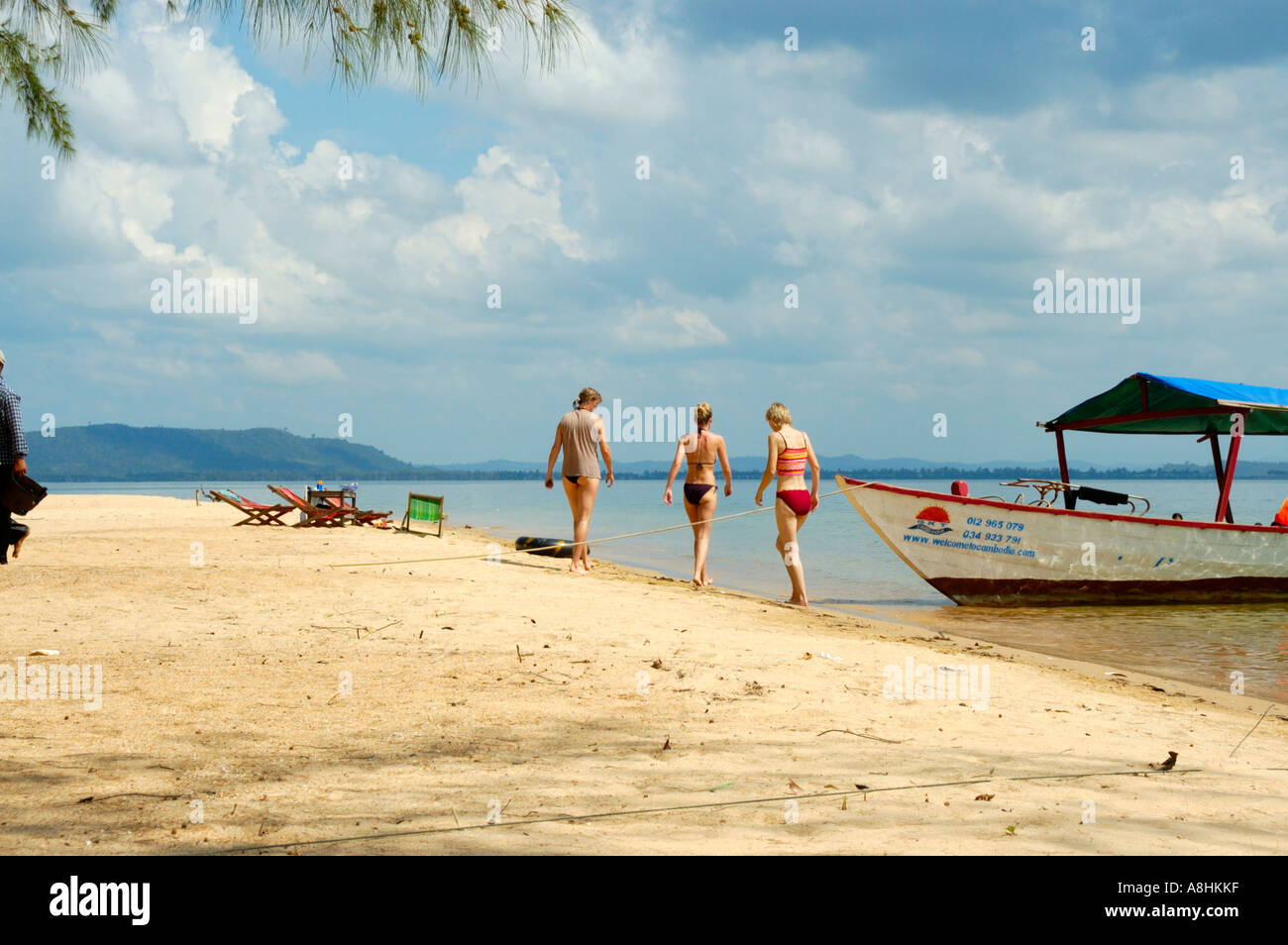 Three young lean women at a sandy beach with a boat Bamboo Island Sihanoukville Kompong Som Cambodia - Stock Image