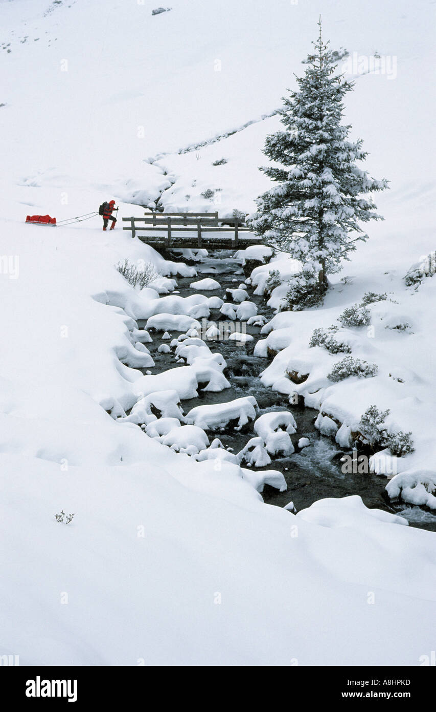Woman snowshoeing and pulling a sledge in Sellrain valley Austria Stock Photo
