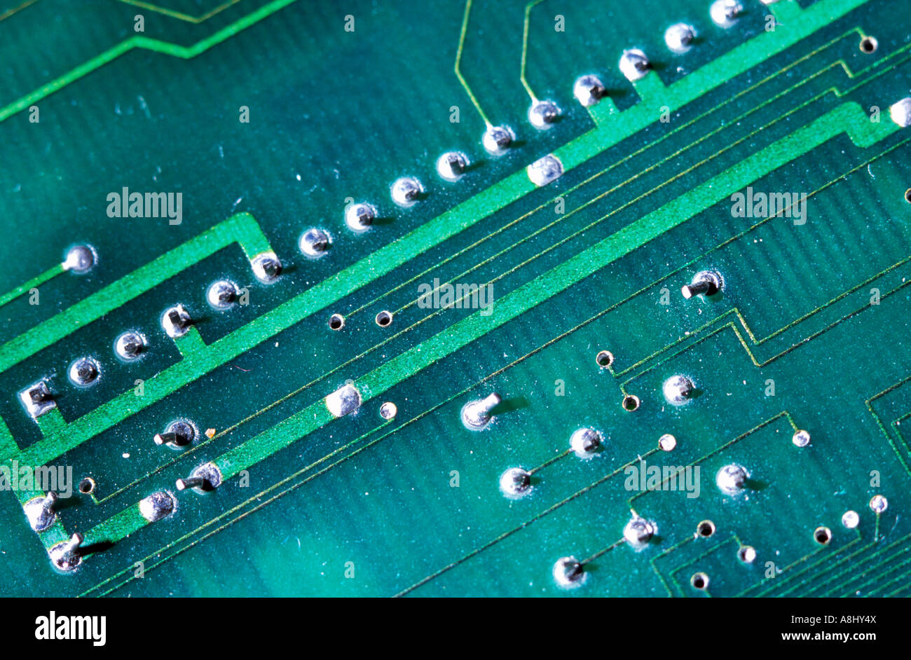 Electronics printed circuit board showing conductive traces and through hole connections - Stock Image