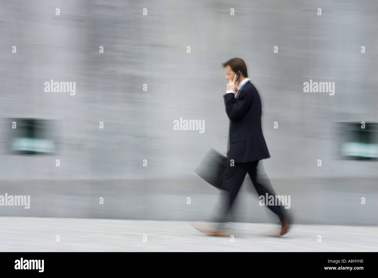 Blurred picture of an huried up business man with executive case in front of an high concrete wall in Munich - Stock Image