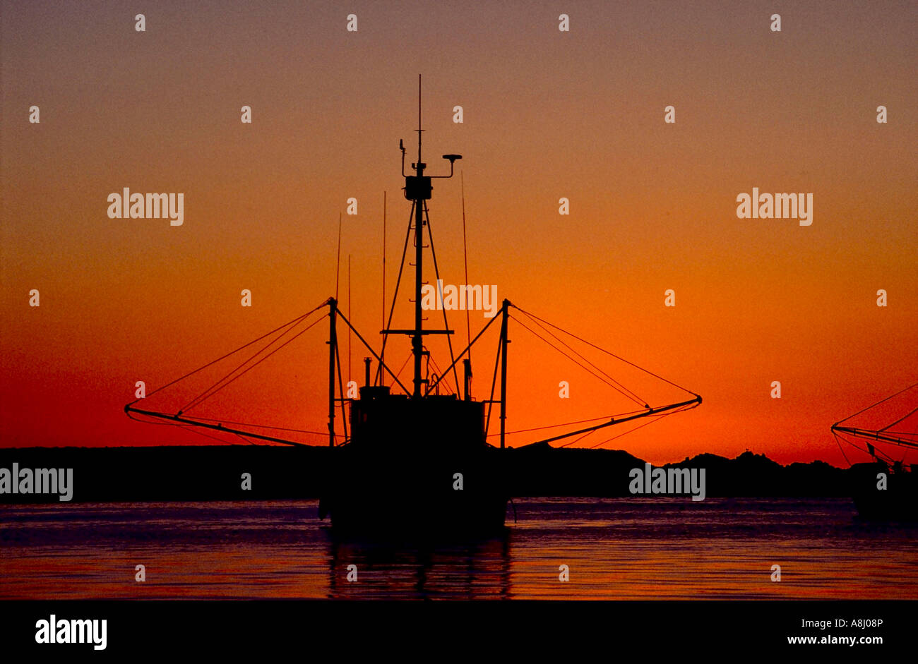 Fishing trawlers at sunset, silhouetted in dusk light Stock Photo