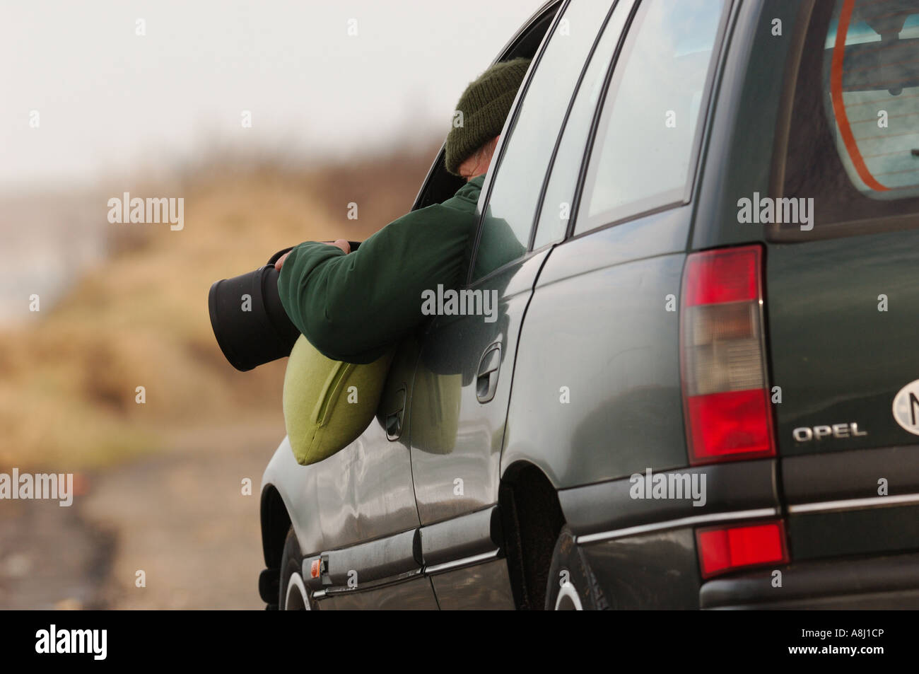 Photographer shoot a picture from out the car with big Nikon Lenses 500mm D200 Opel green waggon - Stock Image