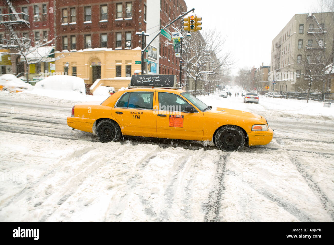 A yellow cab drives through a snow covered street in Harlem after a blizzard in New York City USA February 2006 - Stock Image