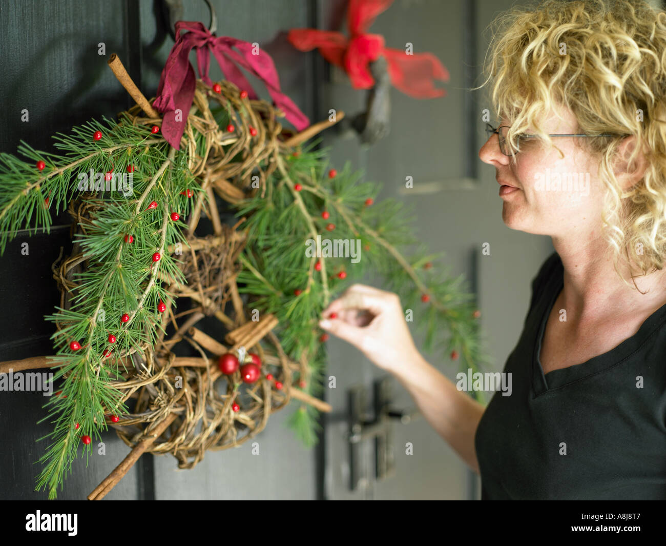 young woman dressing the front door with wreath decoration preparing for christmas guests - Stock Image