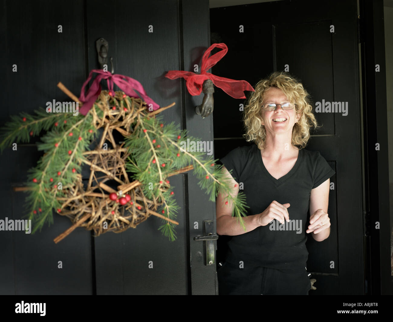 young woman at the front door with wreath decoration greeting christmas guests - Stock Image