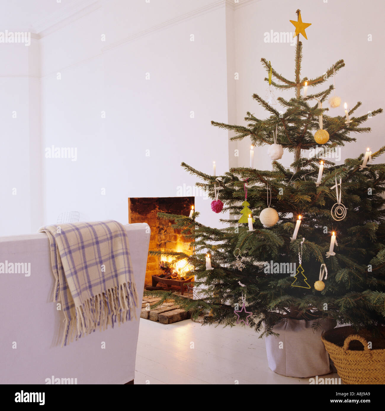 Decorated Christmas tree by open fireplace - Stock Image