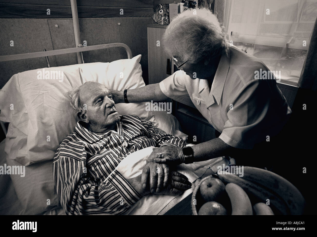 Visiting carer wife companion comforts elderly gentleman in his care home bed Black and White toned treatment - Stock Image