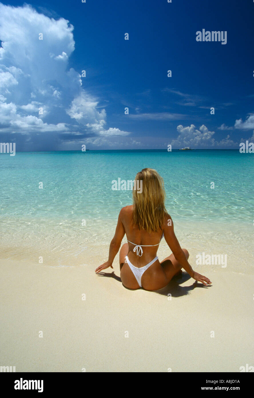 Cayman Islands Grand Cayman woman in thong sitting on