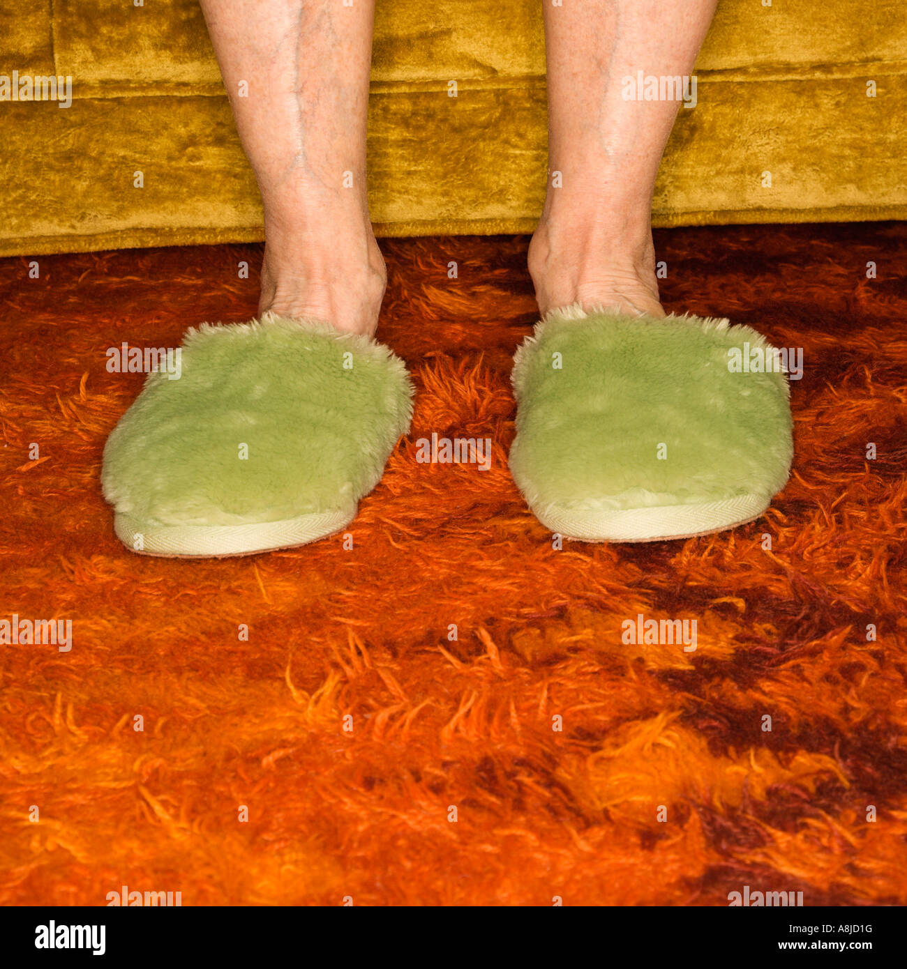 Caucasian senior female feet wearing green bedroom slippers on carpet - Stock Image