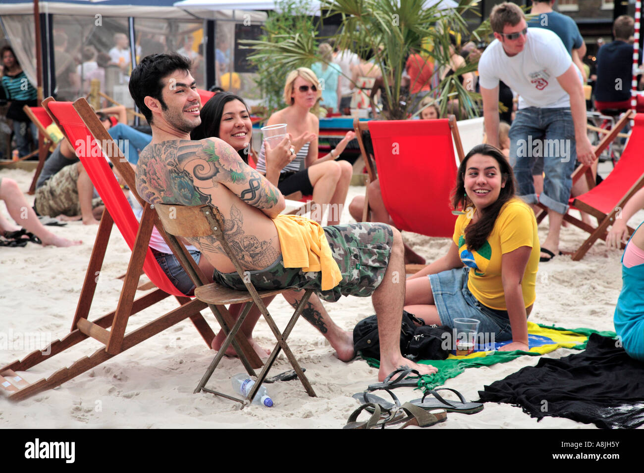 a group of friends relax on a city beach in brick lane, east london - Stock Image