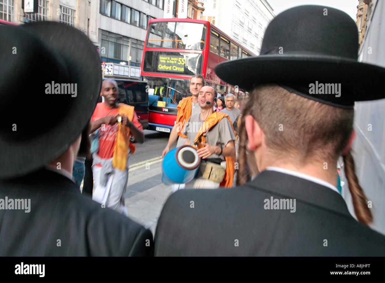 two orthodox jewish men walk past some Hare Krishnas on Oxford Street, London - Stock Image