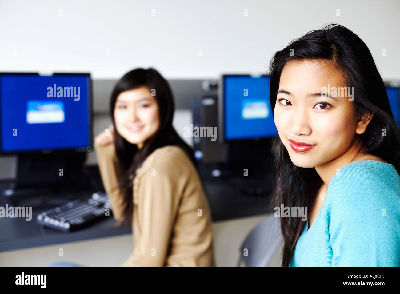 Portrait of two young women sitting in front of computers and smiling Stock Photo