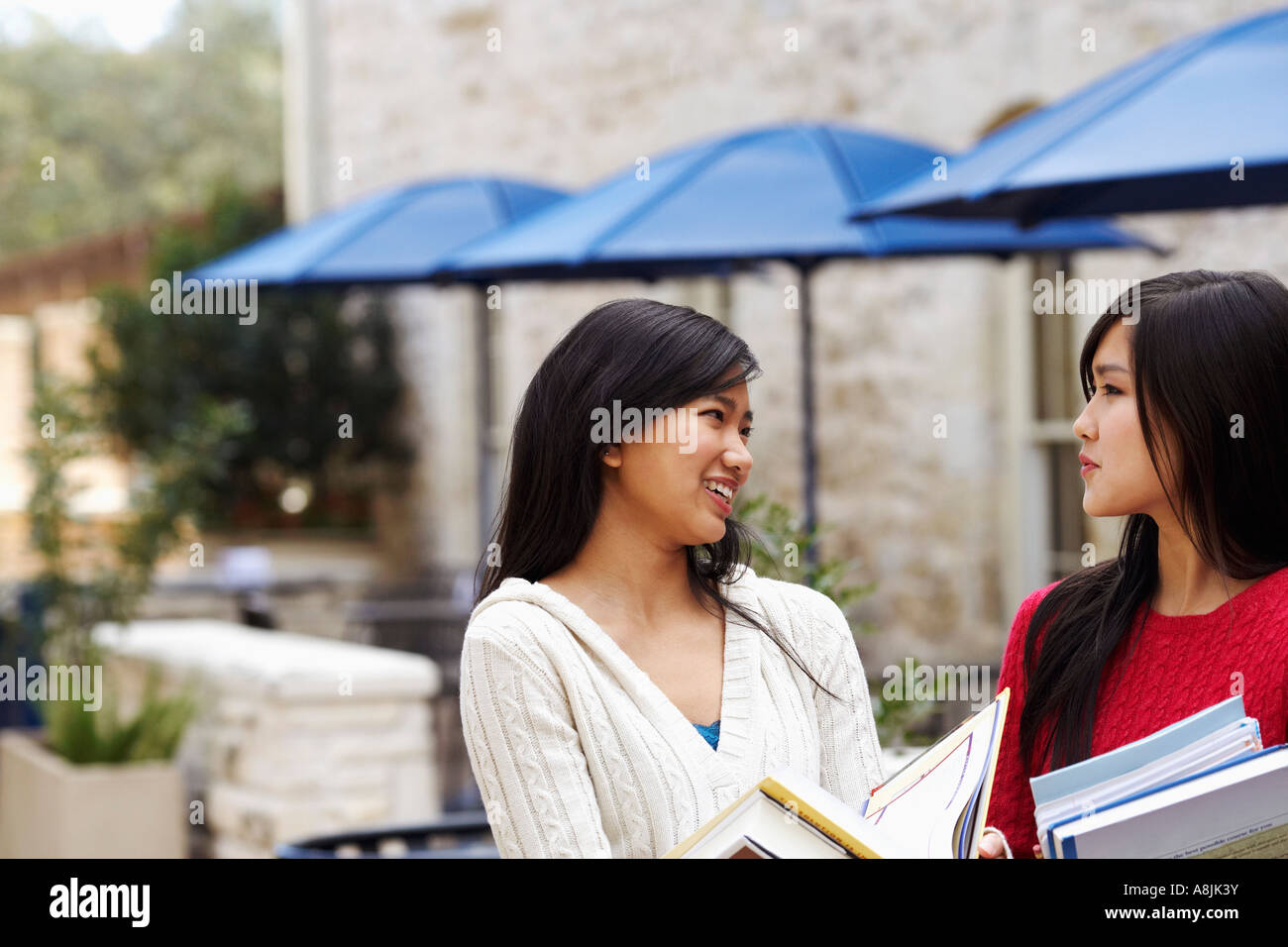 Two young women talking to each other - Stock Image