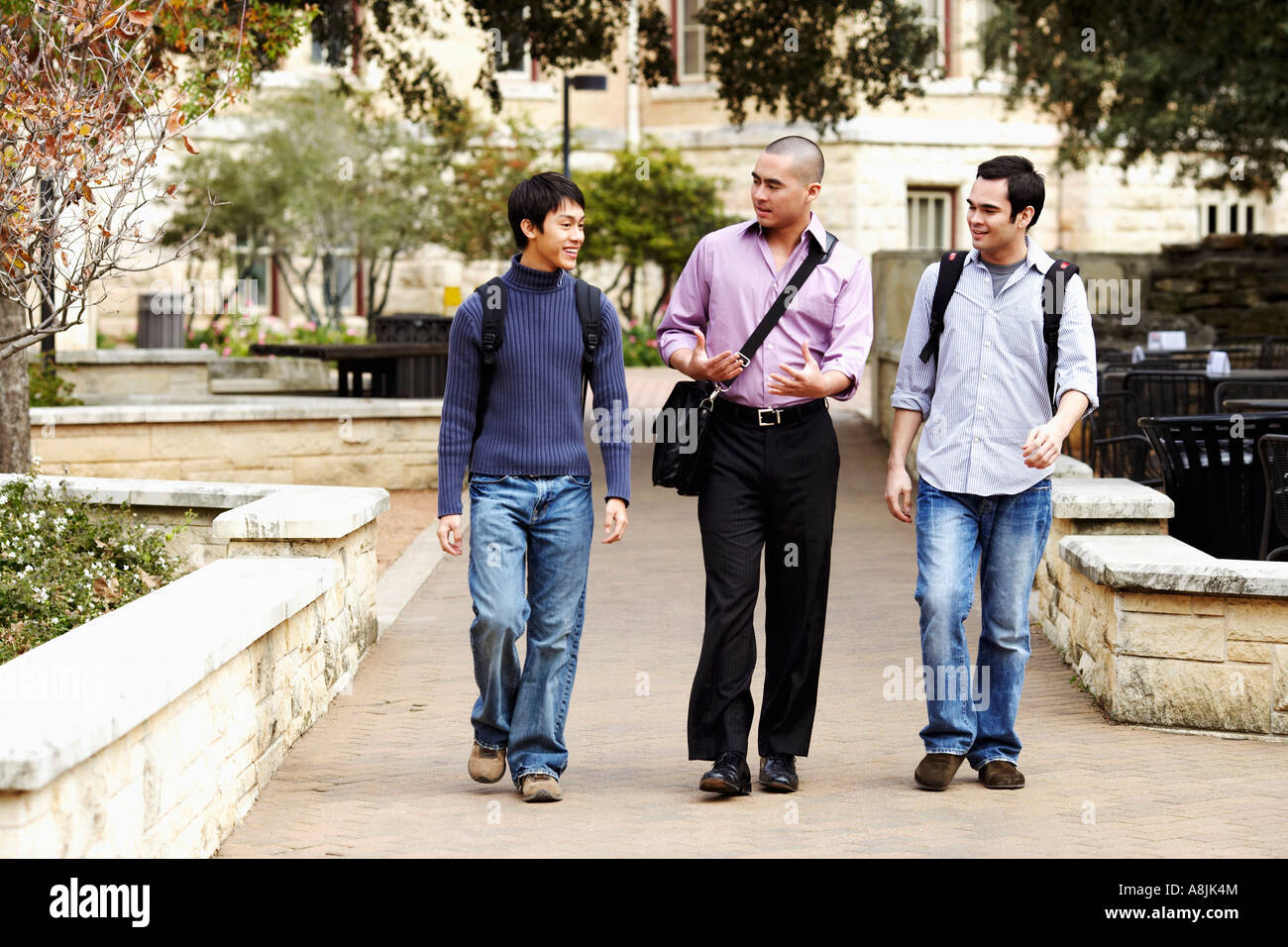 Three young men walking in a college campus and talking - Stock Image