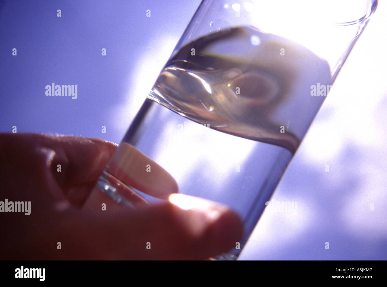 hand holding glass containing water outdoors in sunshine Stock Photo