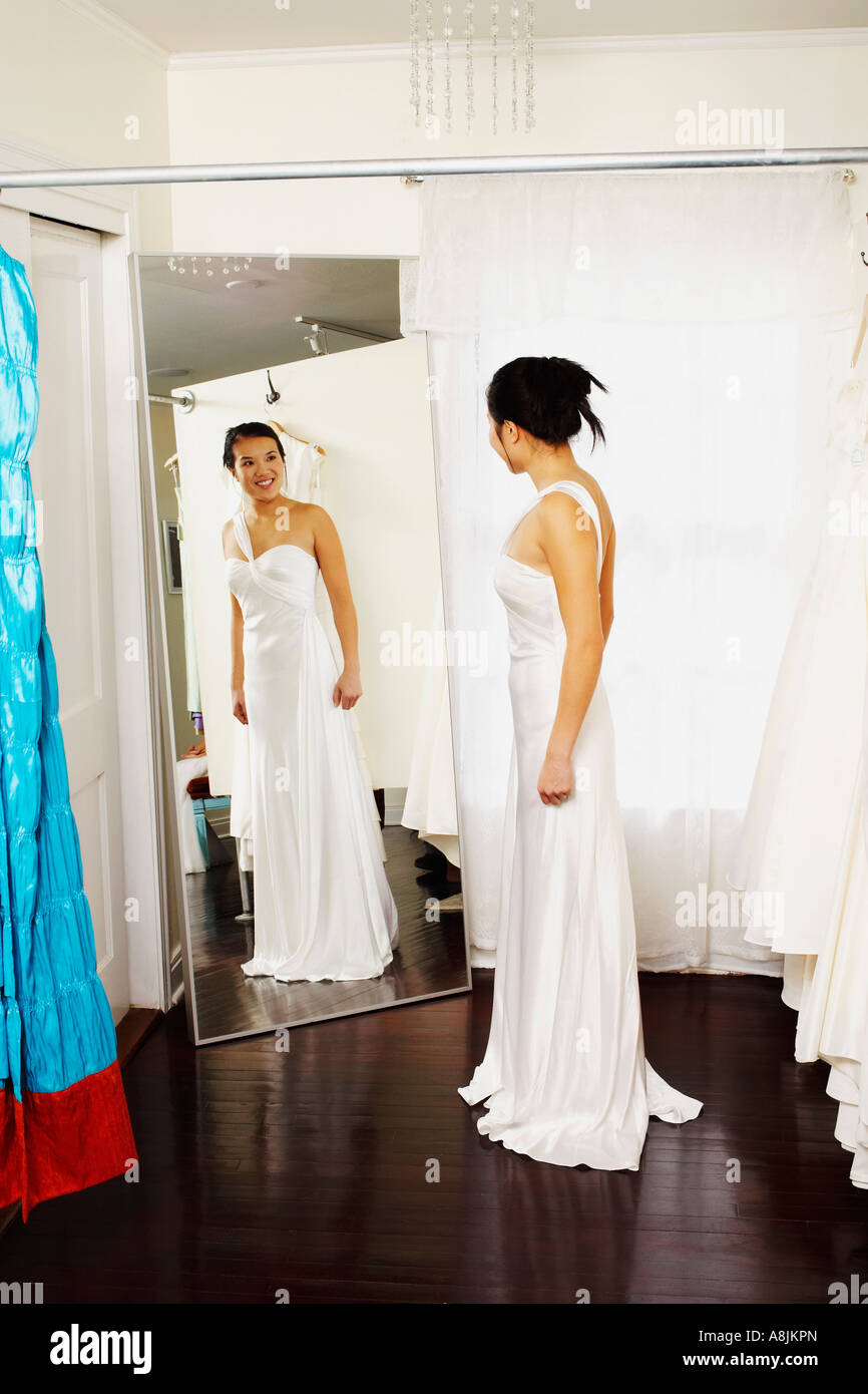 Young woman wearing a wedding dress and looking at herself in the ...