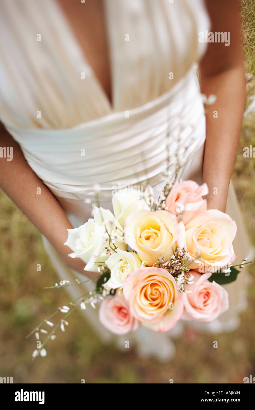 Mid section view of a bride holding a bouquet of flowers - Stock Image