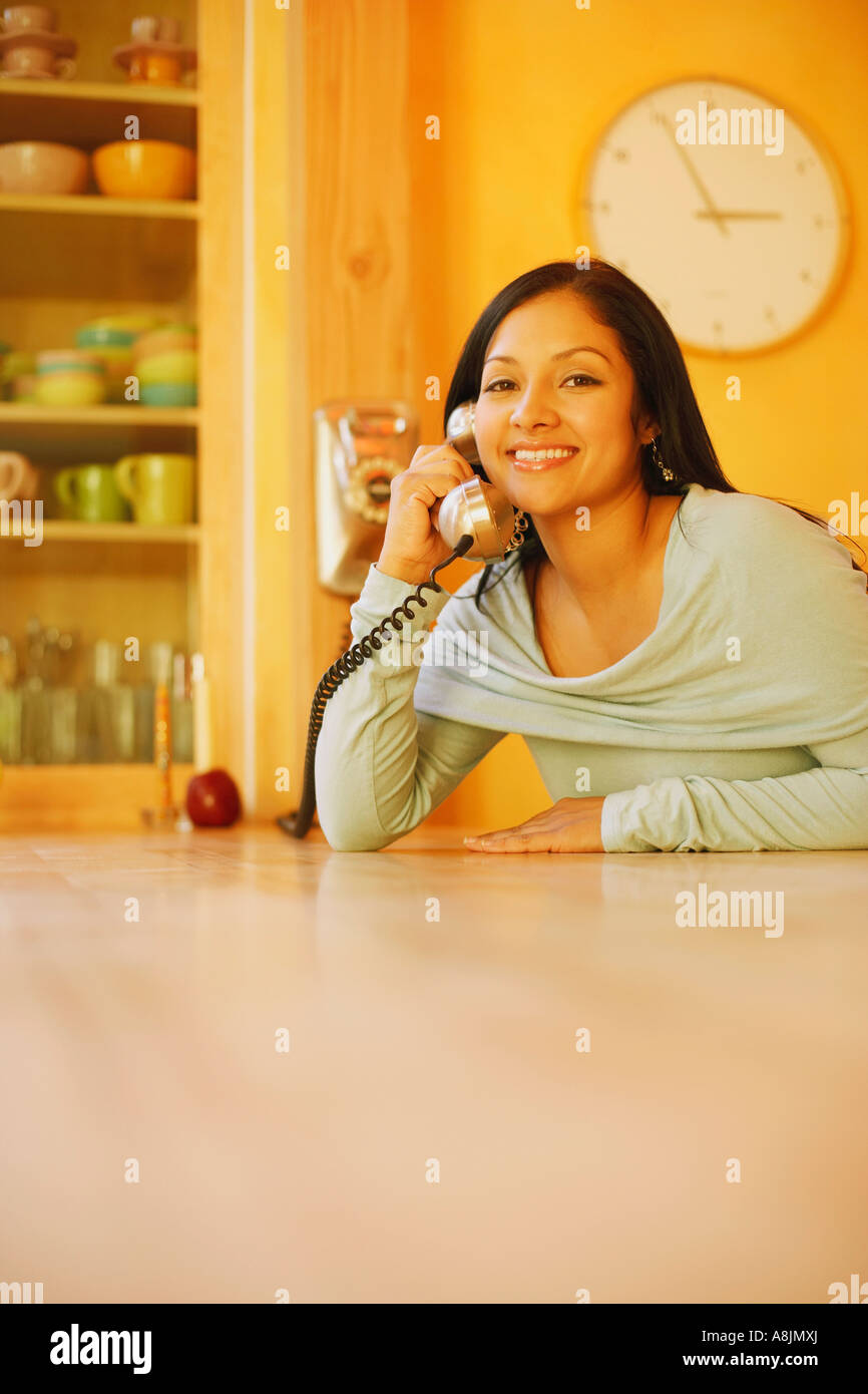 Portrait of a young woman using a telephone and smiling - Stock Image