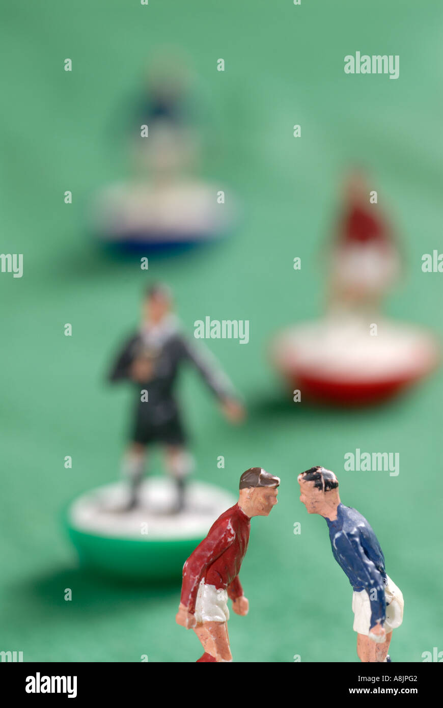 Subbuteo, two table football players confront one another looked over by referee - Stock Image