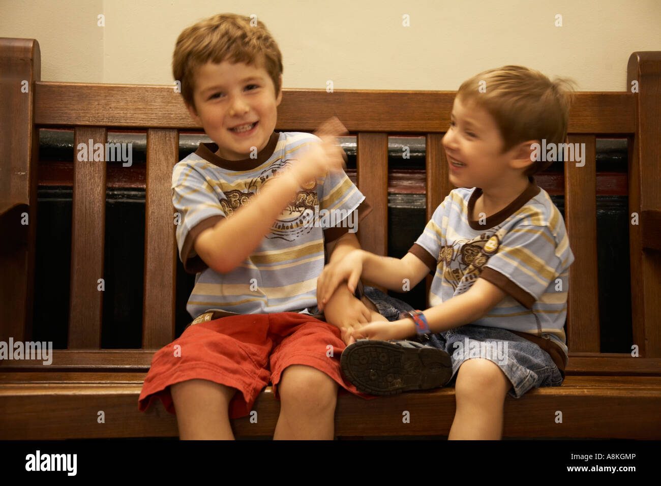 Two young boys children brothers wearing shorts and T shirts sitting on a bench playing fighting laughing Stock Photo