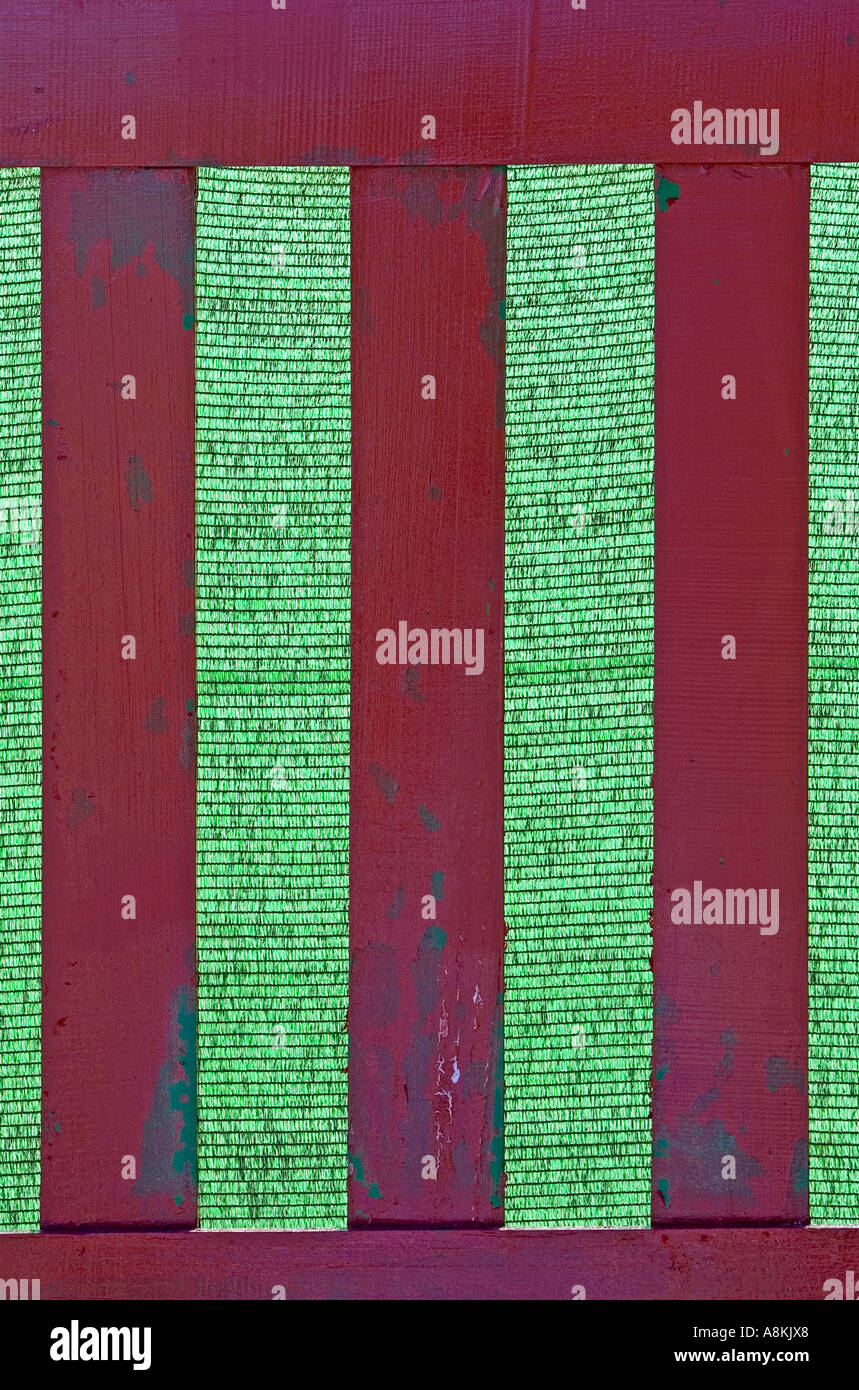 Wooden fence with green background that looks like cricket stumps or roman numerals for three - Stock Image